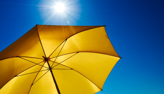 Yellow Umbrella With Bright Sun And Blue Sky Picture Id936342386