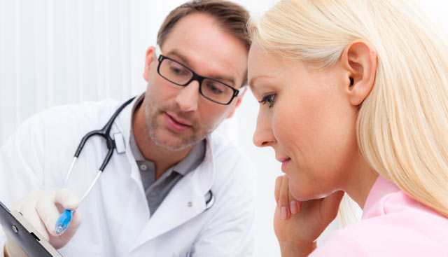 Doctor going over a skin cancer diagnosis with patient with blonde hair and fair skin